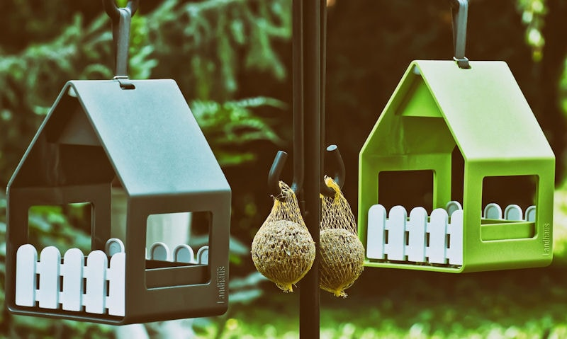 Metal bird feeders hanging off feeding station, brand name seen engraved on feeder