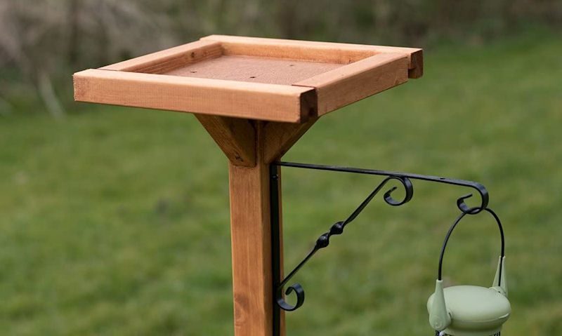 Wooden open bird table top seen with hanging bird feeder bracket