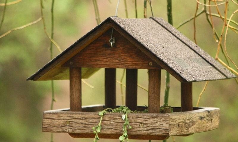 Hanging wooden bird table with roof, supported with four pillars